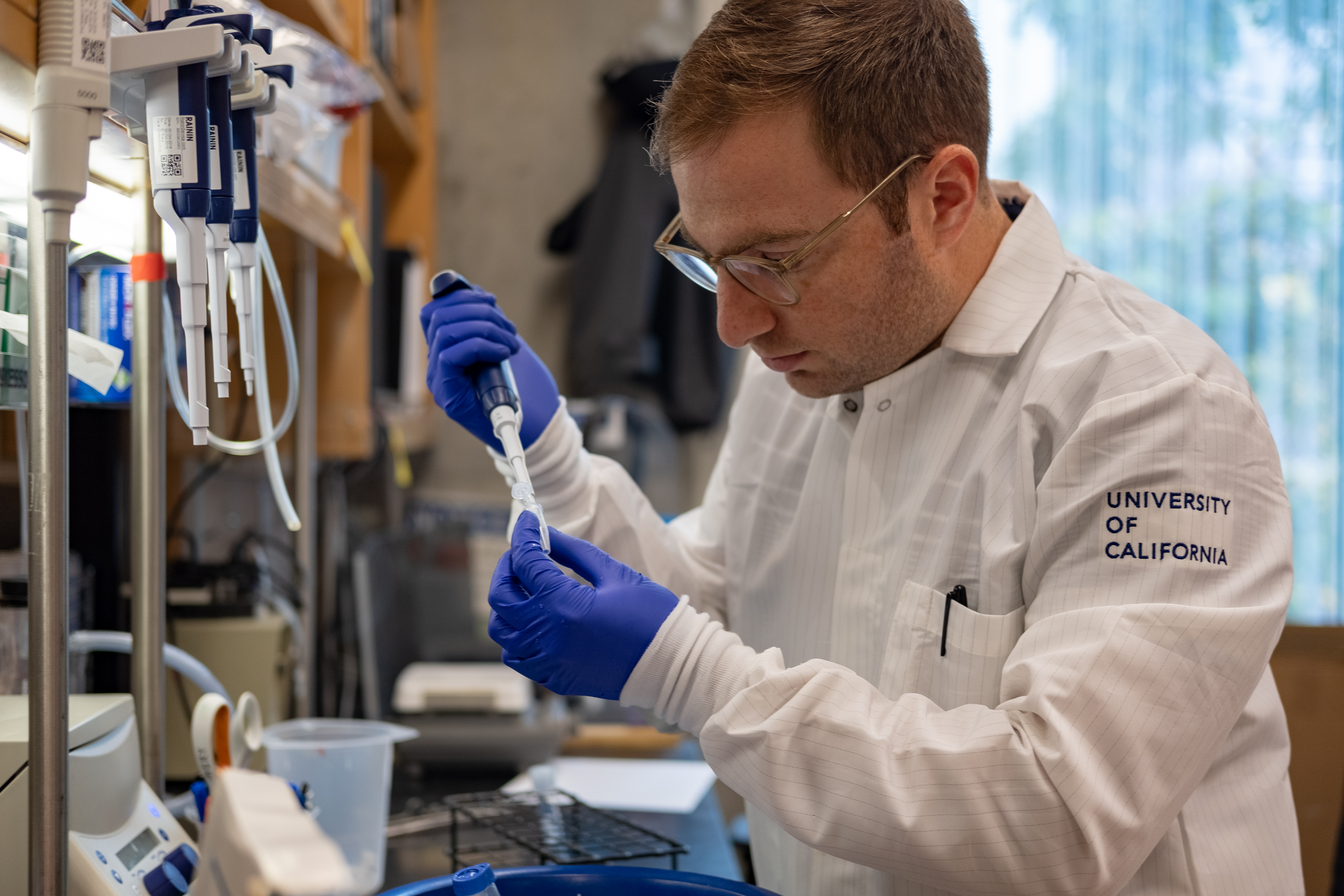 Man wearing lab gloves and a lab coat using a pipette
