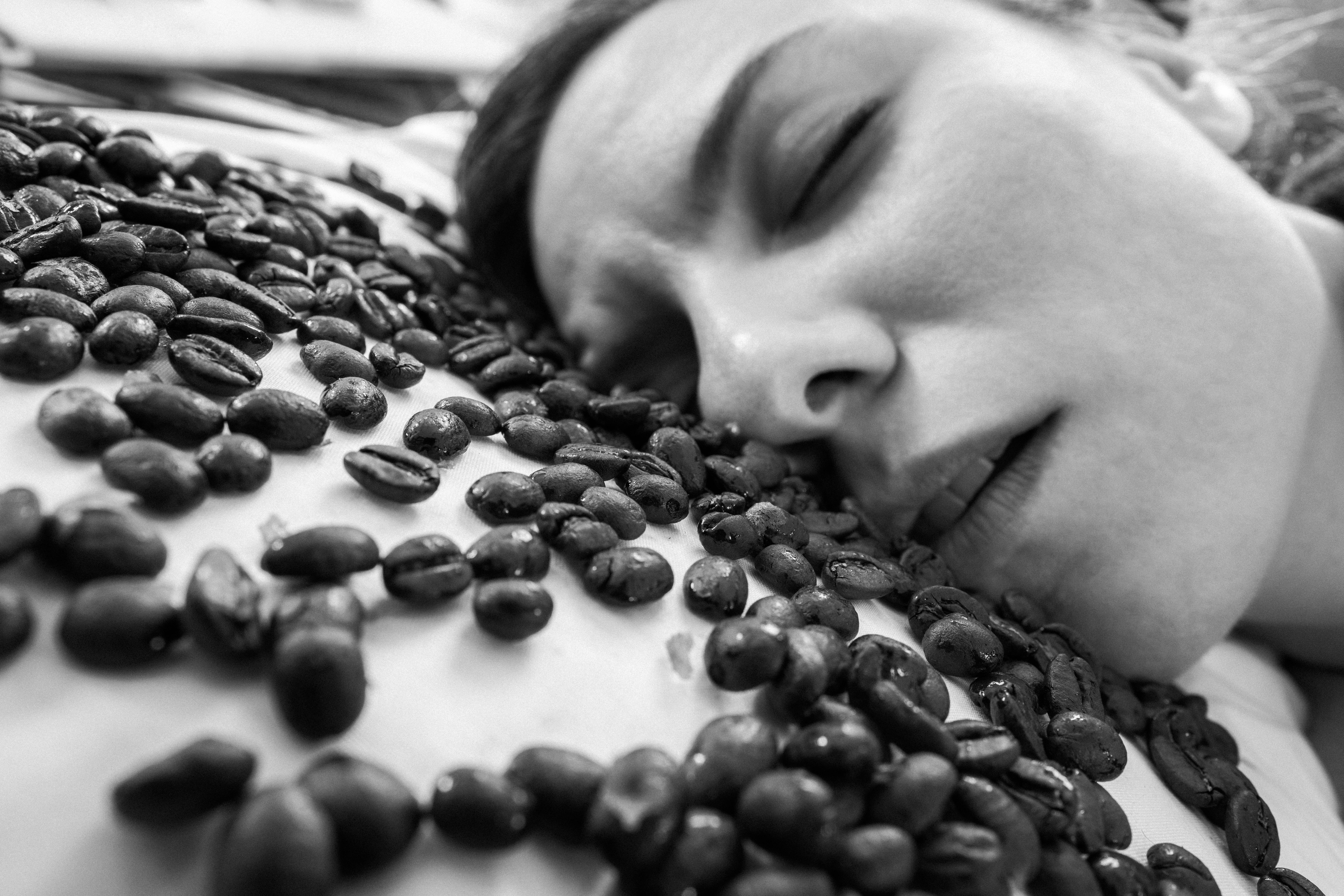 Woman asleep on a table of coffee beans