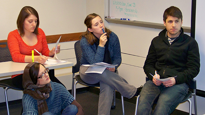 """Illinois State students Ashley Toenjes, below left, Alex Trimble, left, Raina Kirchner, and Jeff Koch prepare the presentation of their class's report: """"Food Insecurity in Bloomington-Normal: How a Grocery Cooperative Might Help Meet the Needs of Low-Income Residents."""""""