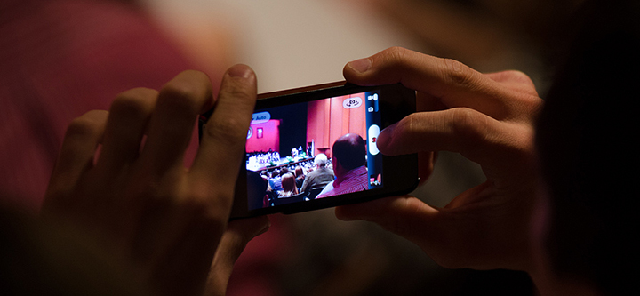 A parent uses a phone to capture the 2013 Commencement.