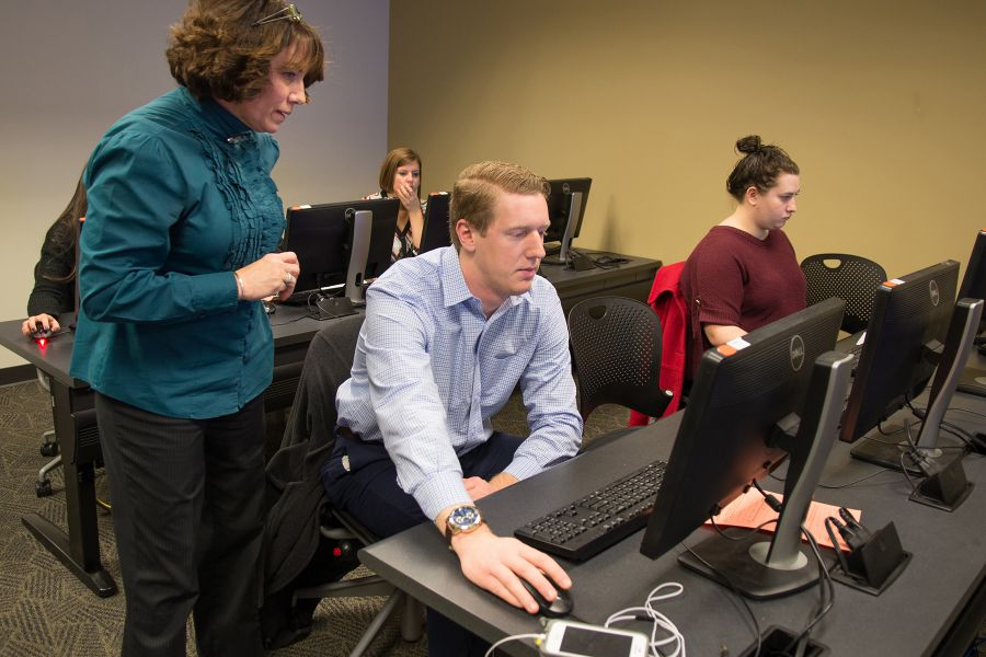 Showers, left, works with a student on Adobe design software. Around 140 students are majoring in integrated marketing communication.