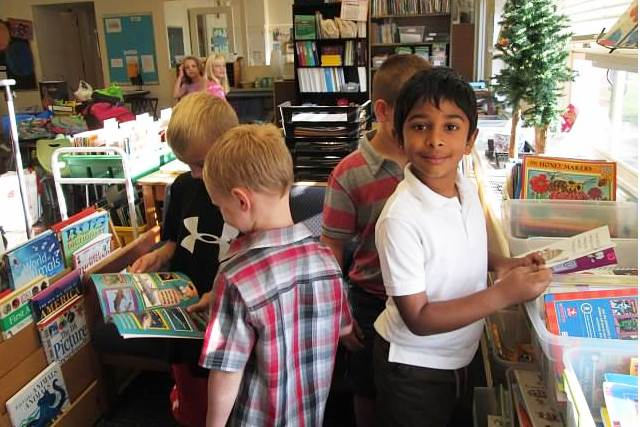 First grade students choose books.