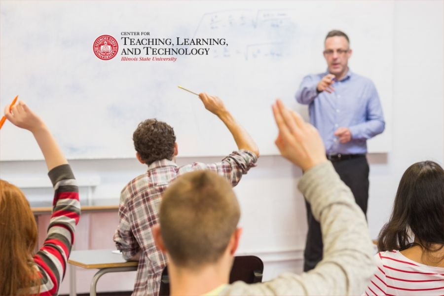 Teacher standing in front of class with raised hands.