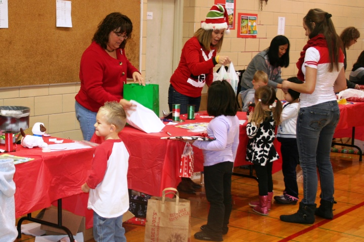 Metcalf students watch as volunteers wrap their gifts during the Holiday Bazaar.