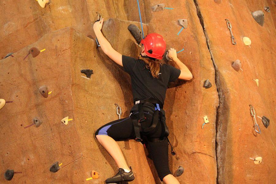 Student climbs rock wall