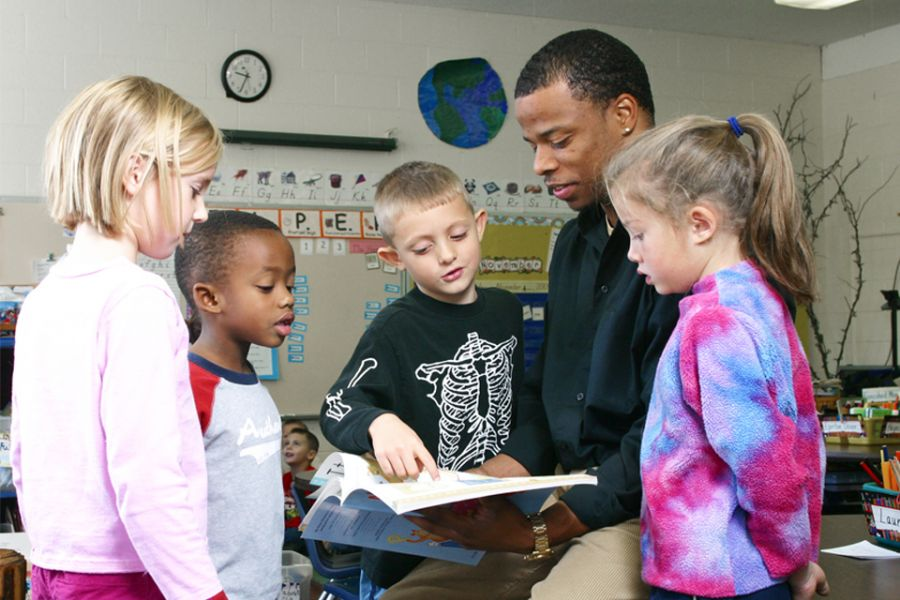 An Illinois State education major collaborates on a literacy lesson with several students.