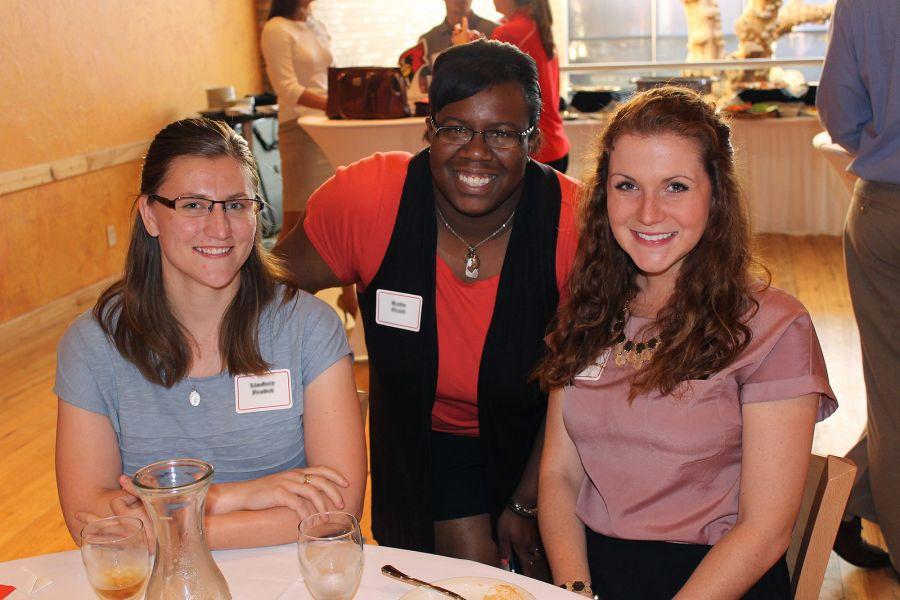 three alumni at table