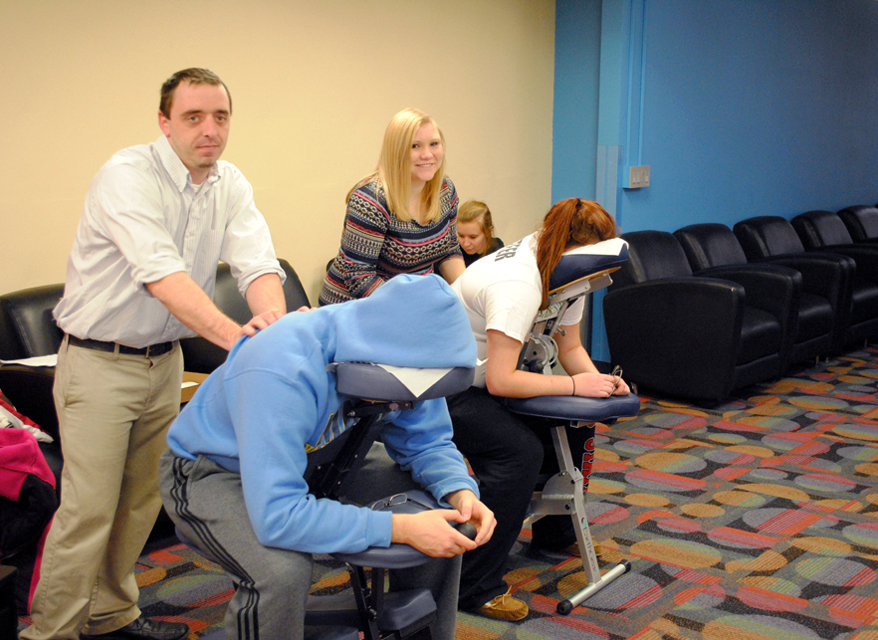 Students in chairs getting massage from therapists