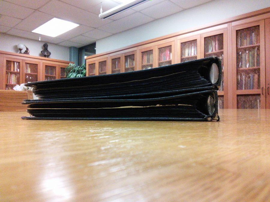 two black binders on wooden desk