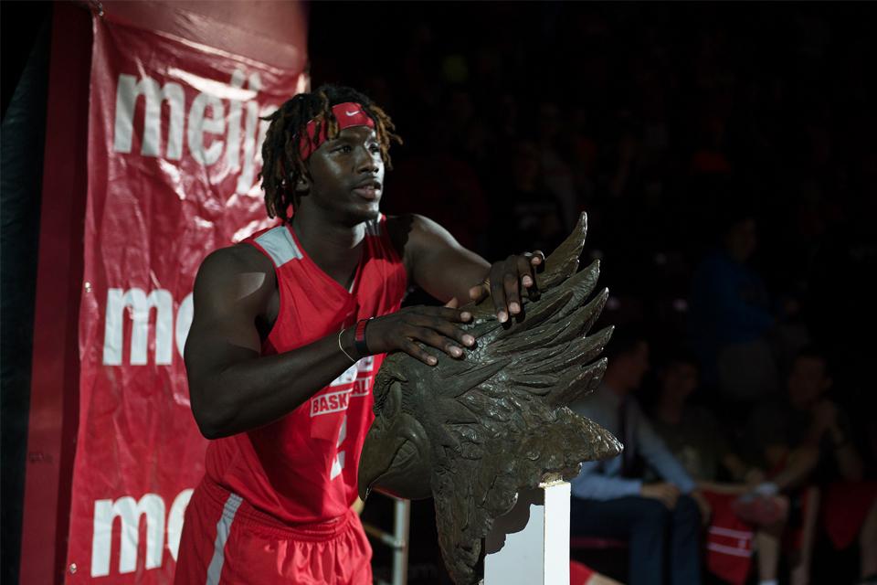 Basketball player touching bust of Reggie Redbird