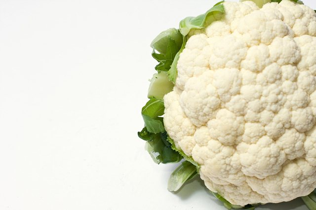 Part of a white cauliflower with leaves on the side