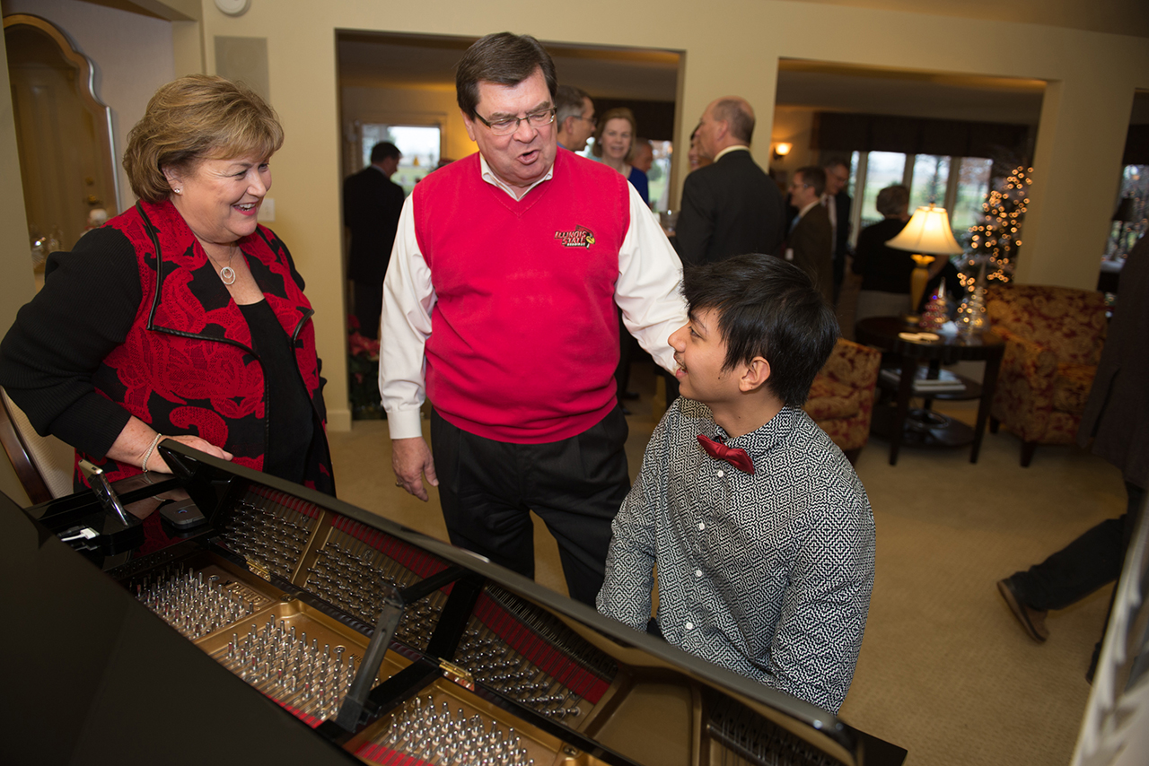 University President Larry Dietz and his wife, Marlene, talk to School of Music pianist Dominique Gonzales at an event December 13 at the University