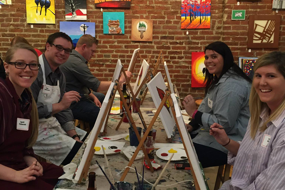 five people sitting in front of canvas