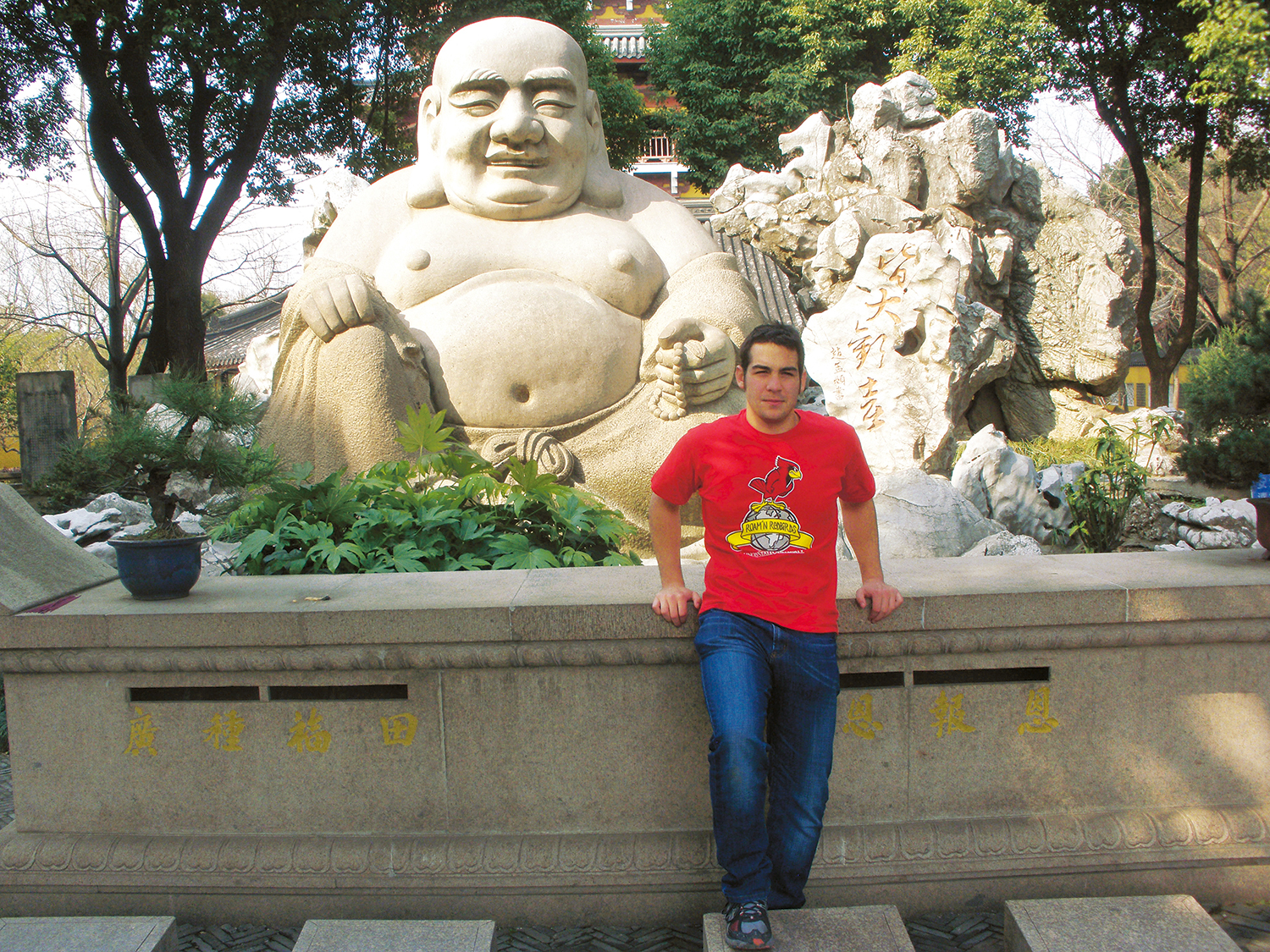 Student poses in front of statue