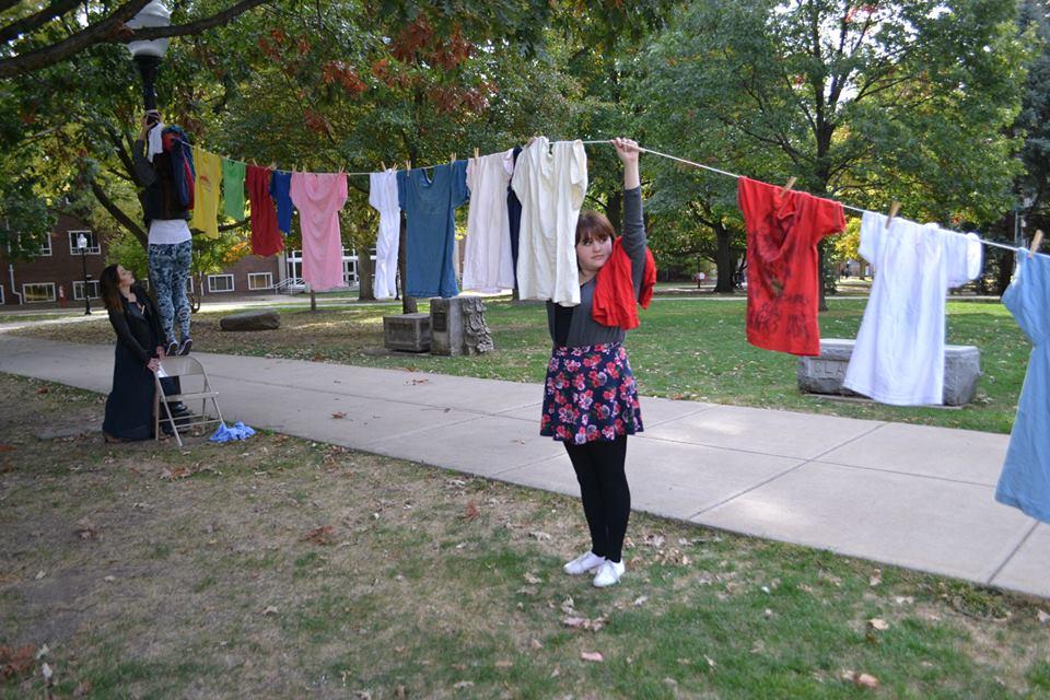 Illinois State student and ISU F.L.A.M.E. member Kristina Harlow helps hoist The Clothesline.