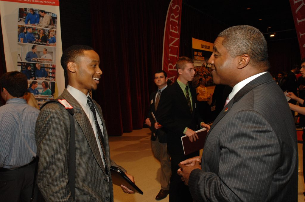 Drew Butts, Enterprise group talent manager (right), talks with an Illinois State student about his experience at a career fair.