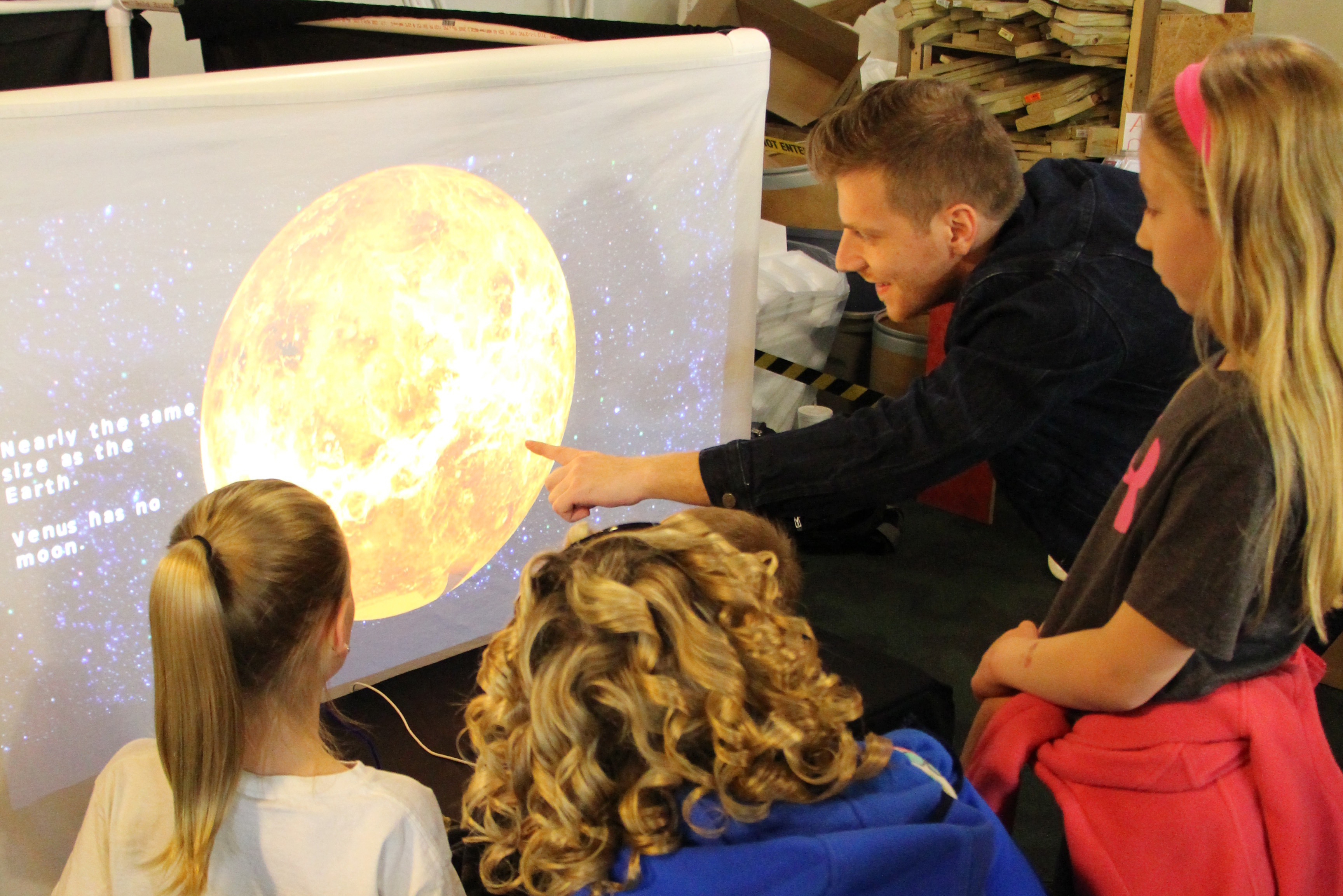 """Arts technology program junior Ion Taflan shows off his group's project, """"Solar System Exploration,"""" at the Children's Discovery Museum."""