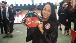 Student holds her mortarboard