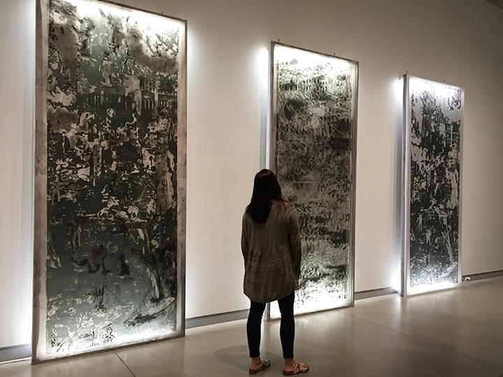 See a woman from behind as she walks past three 12-foot tall multi-layered prints that are lilluminated by florescent lights.