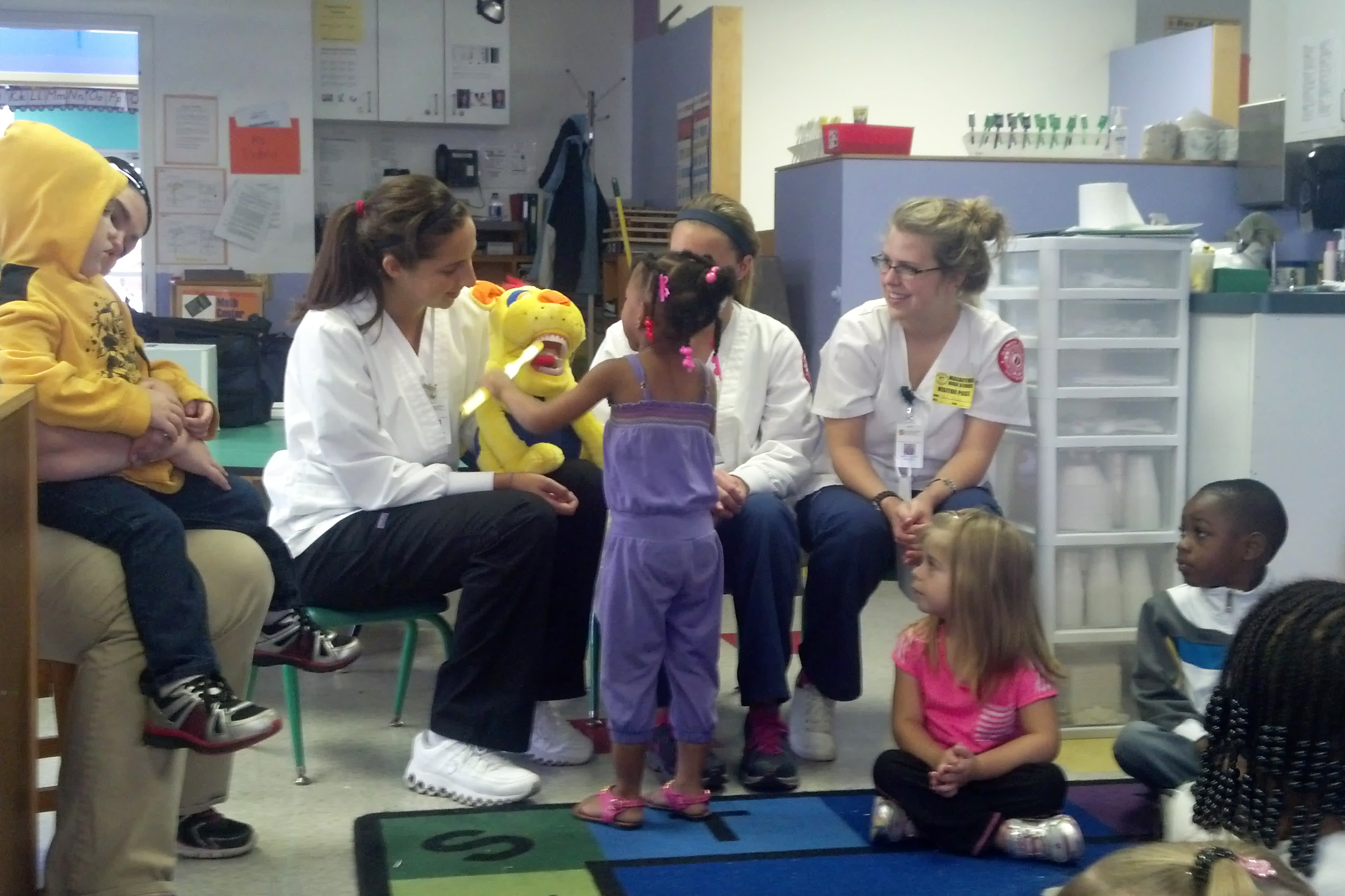 Students teaching with dental dog