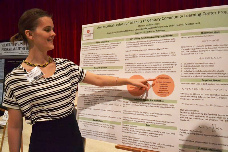 Student points to research poster