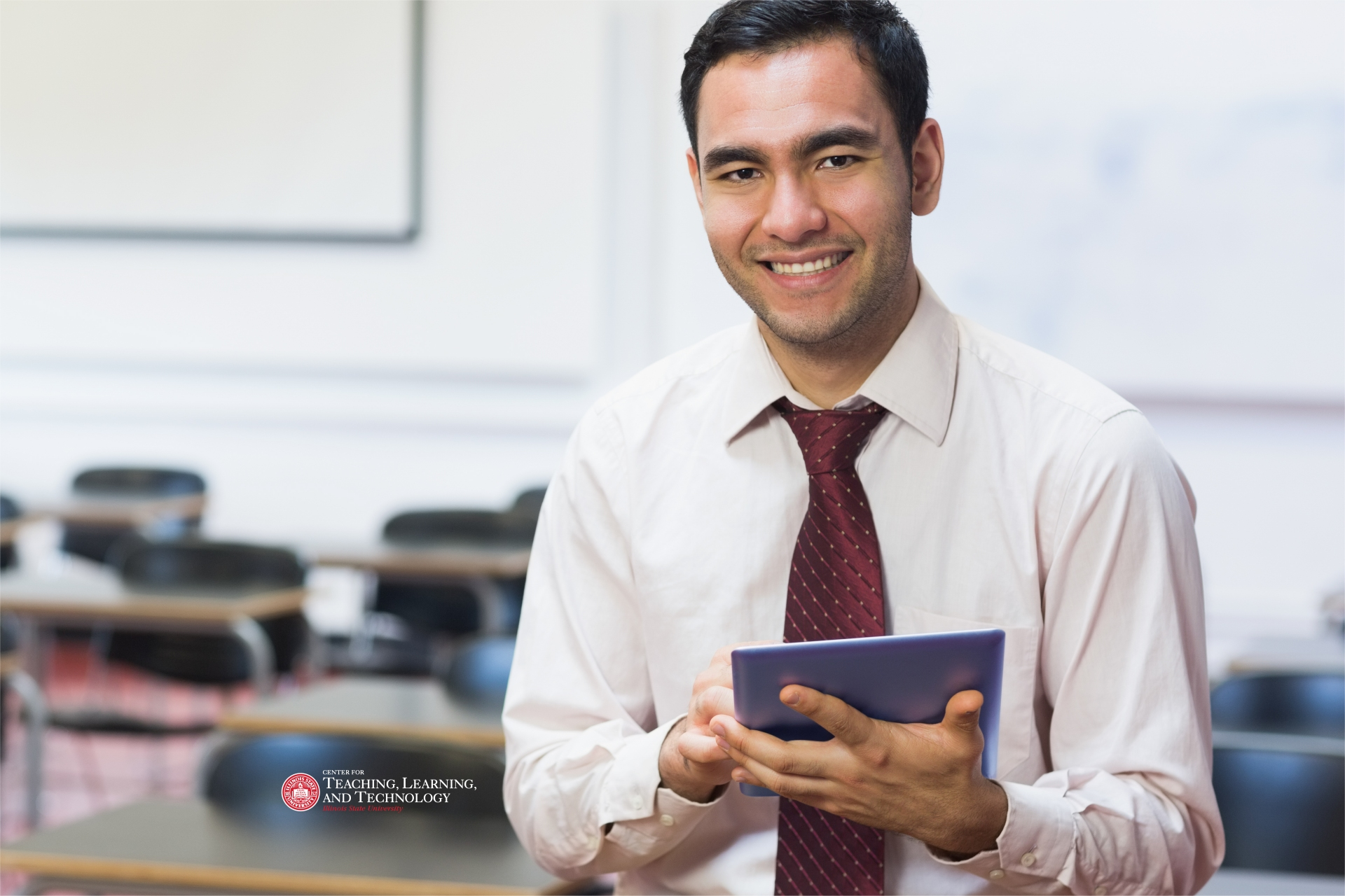 Instructor in empty class, smiling into the camera, holding a tablet device.