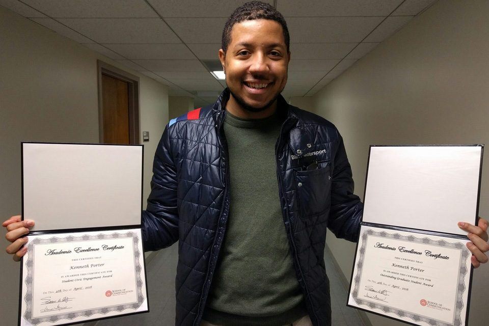 Kenneth Portter stands with two diplomas