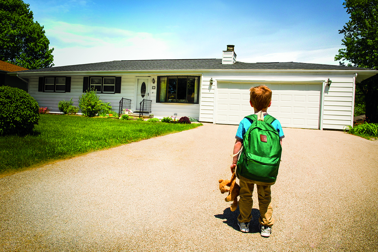 boy in front of home with teddy bear