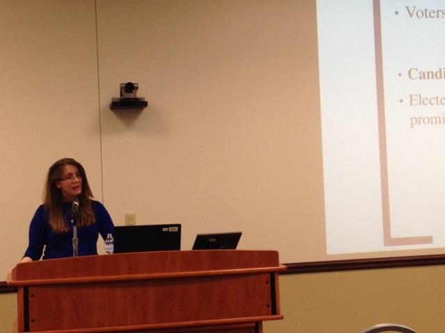 Kerri Milita talking at podium