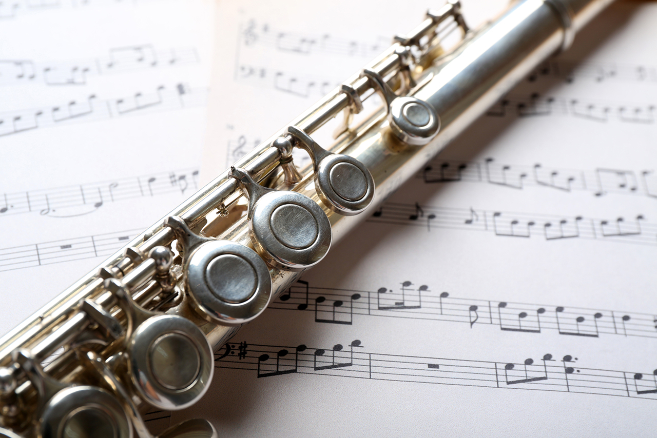 image of Silver flute on music notes background