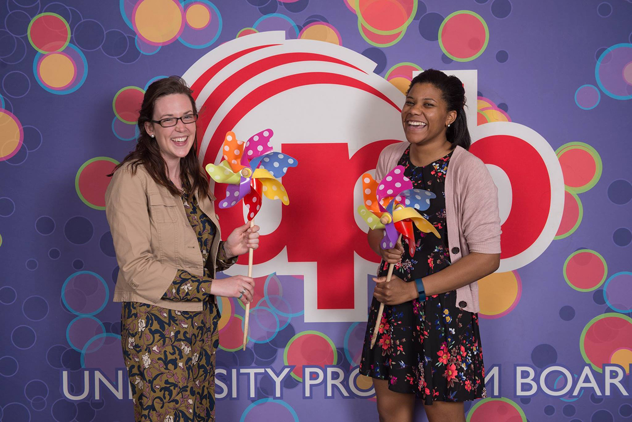 Two female students in front of a wall with a UPB logo