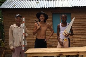 Michael Anstirman (center) with neighbors building a table for his house.