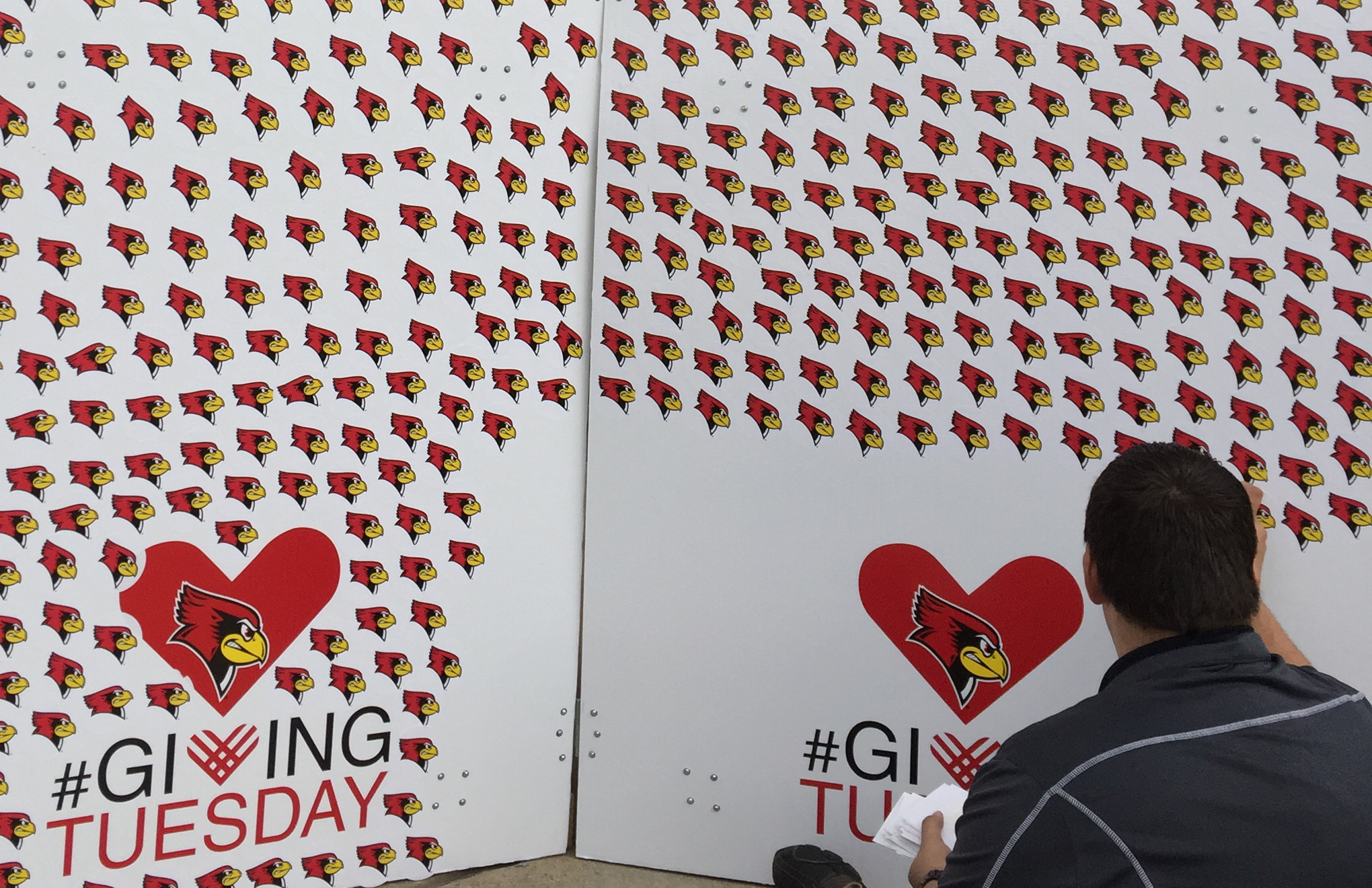 image a student in front of a board filled with Redbird stickers