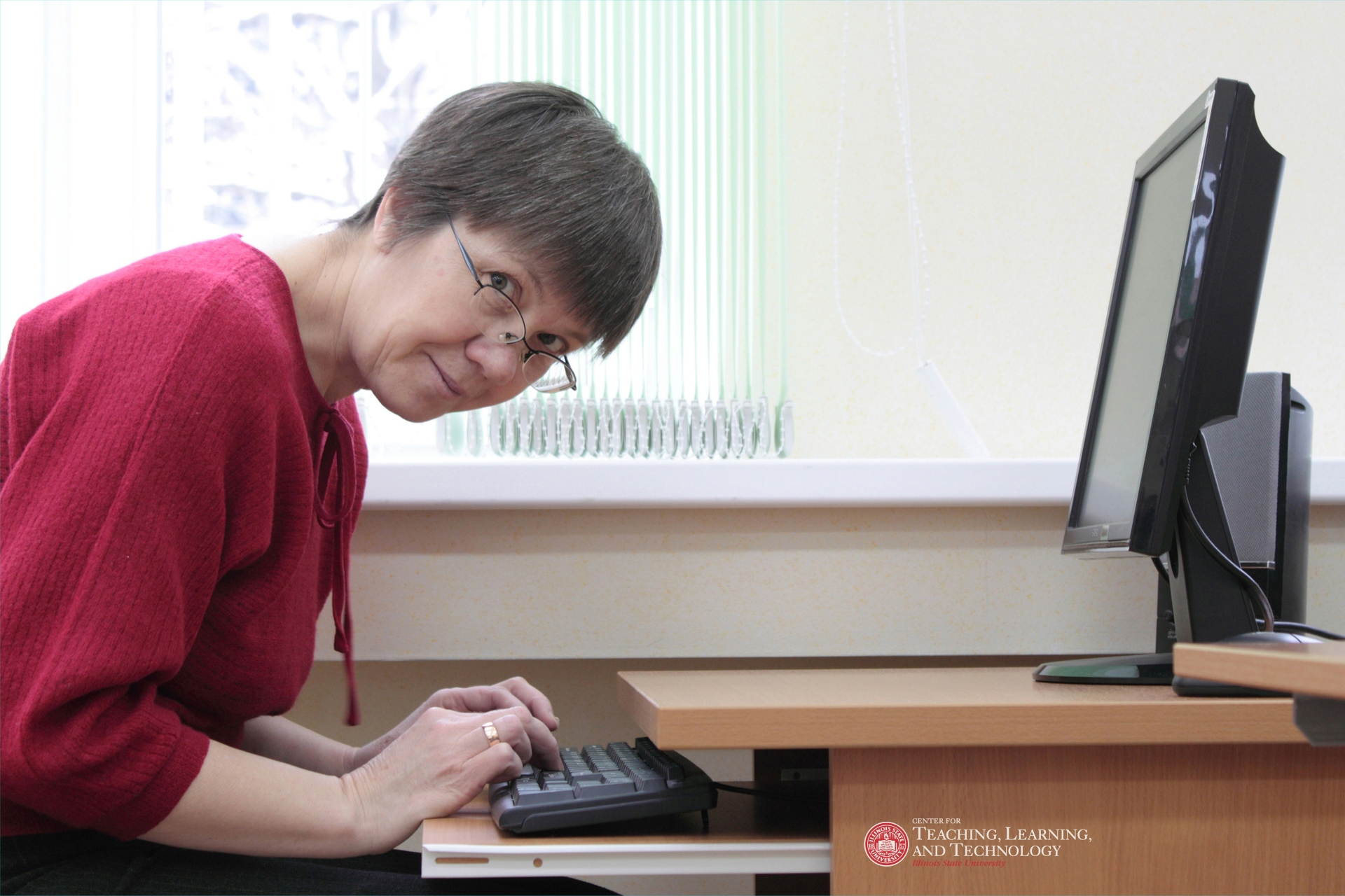 professor looking into camera, sitting at desk