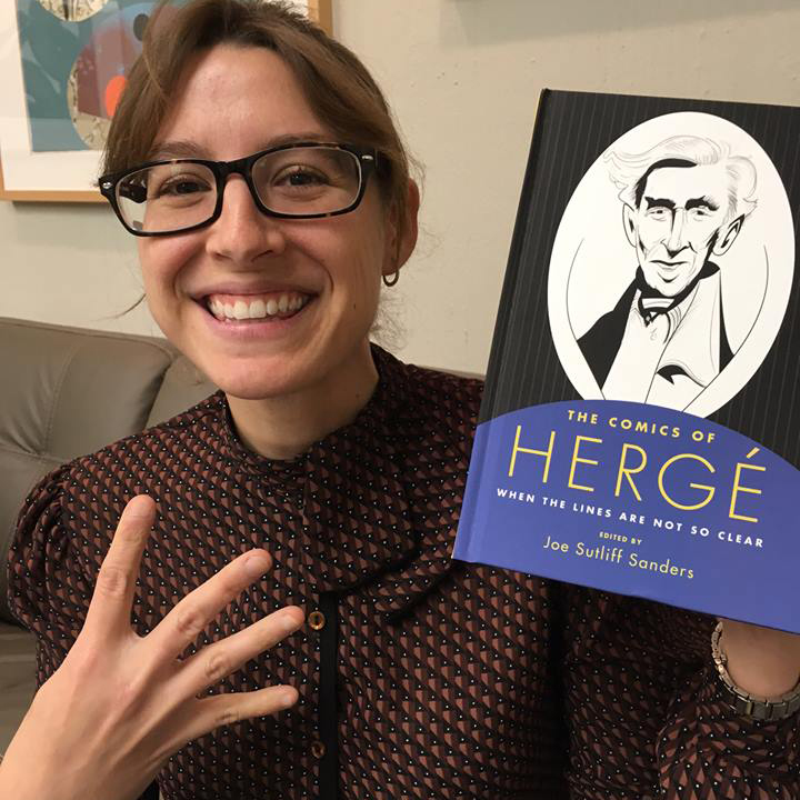 Vanessa Schulman with book and four fingers up