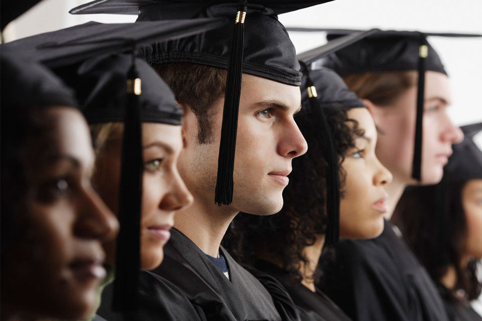 Students lined up wearing mortarboards