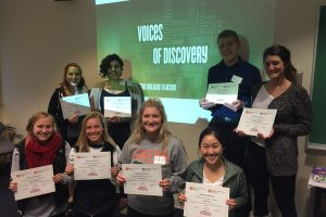 Students pose in front of Voices of Discovery logo