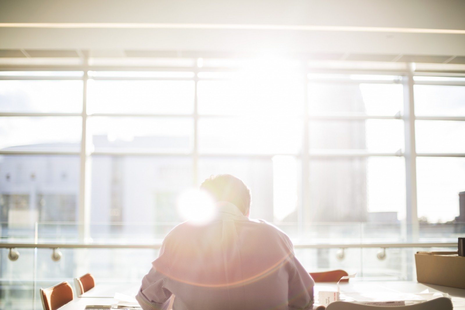Person sitting at desk bathed in sunlight