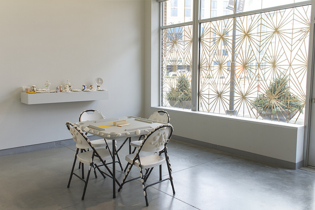 dominos table with seashells attached, geometric design in gallery windows made out of gold metallic tape
