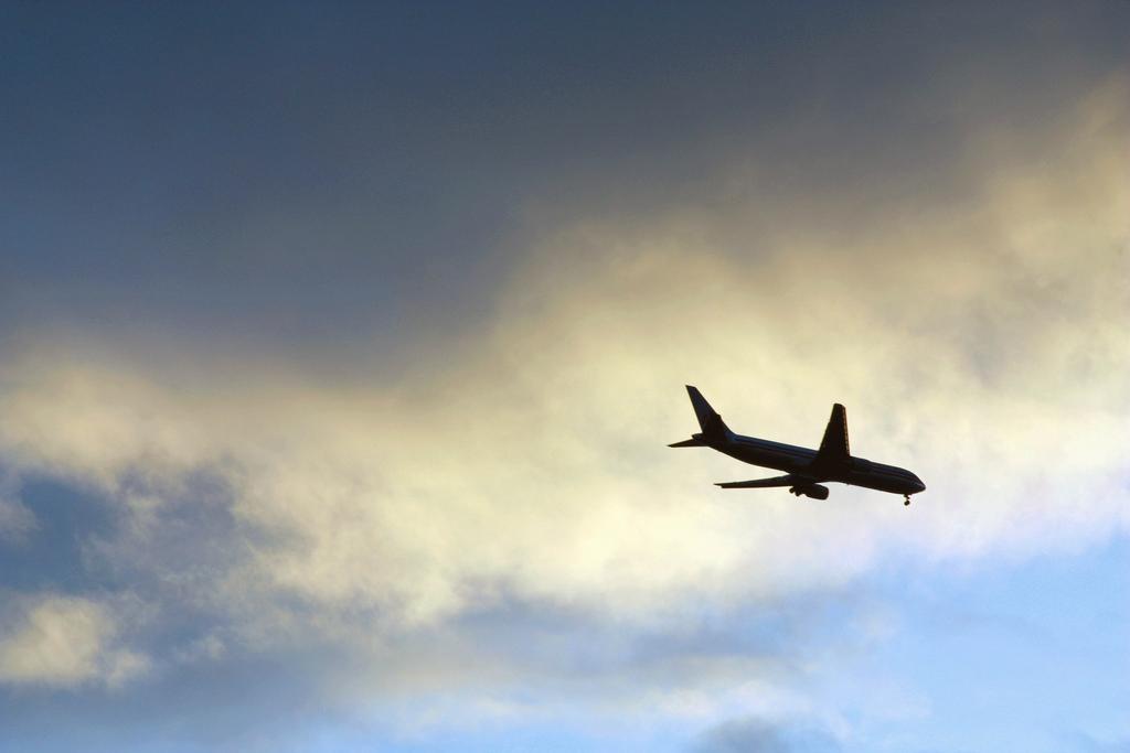 An airplane flies through the sky.