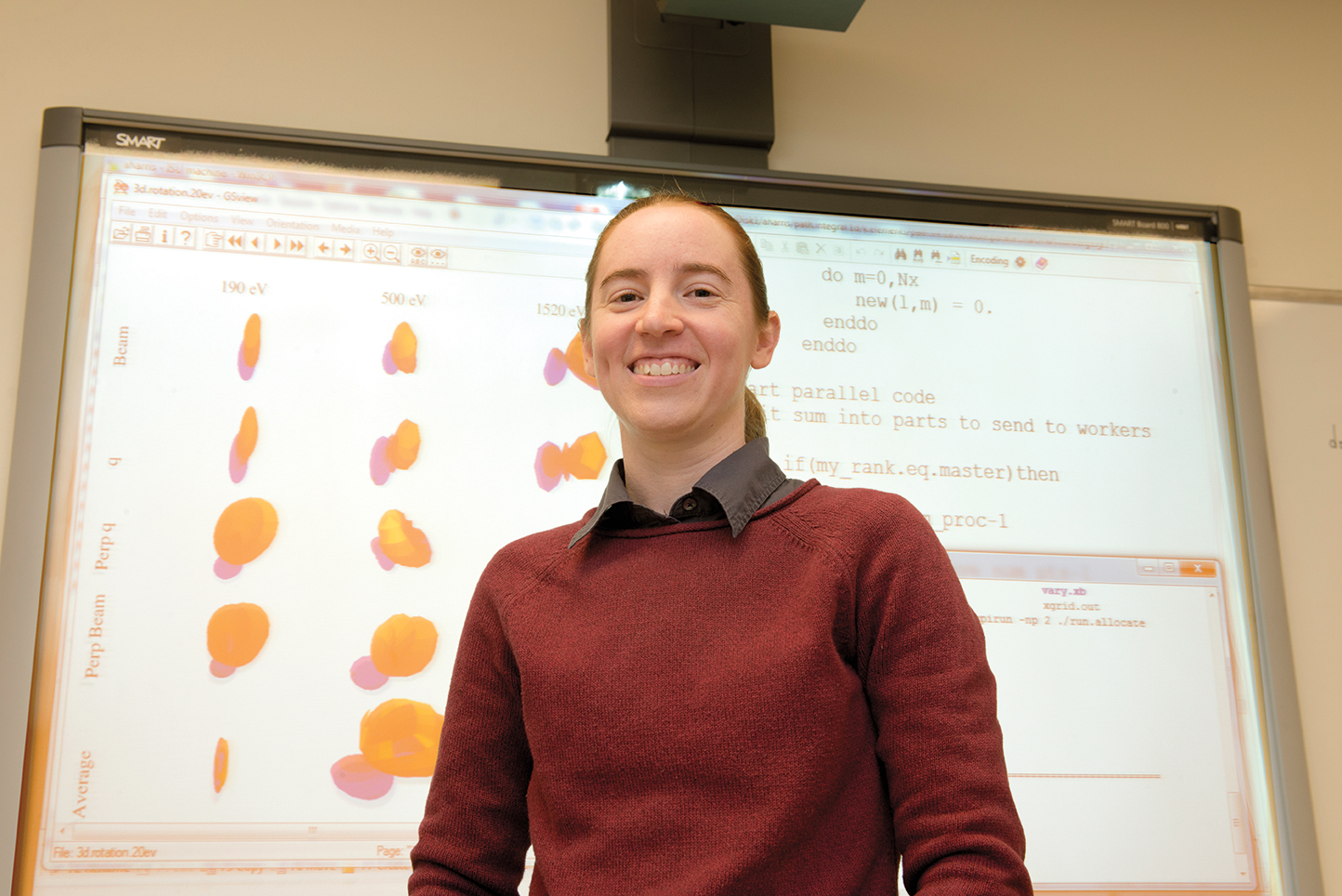 Illinois State Physics Professor Allison Harris standing in front of a whiteboard containing her research.