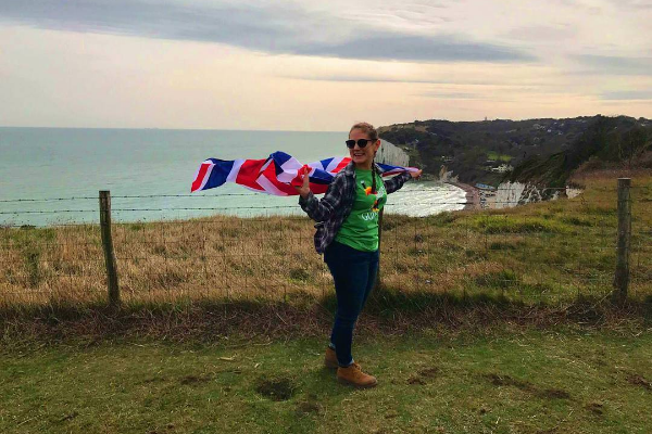 Photo of a student standing near cliff overlooking sea.