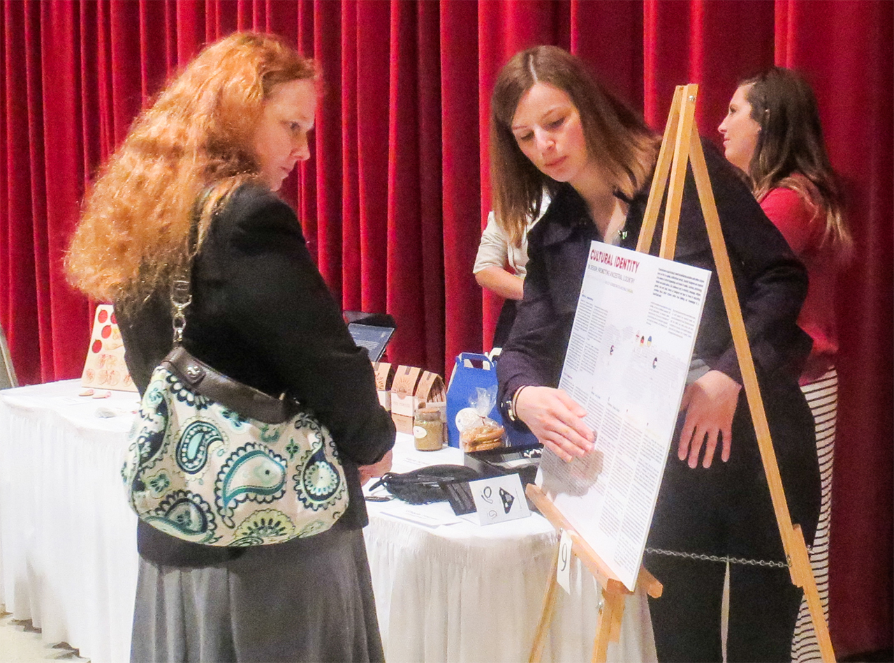 Image of a student displaying research at the University Research Symposium.