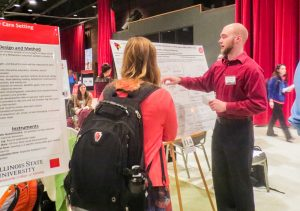 Photo of a student explaining research at the University Research Symposium.