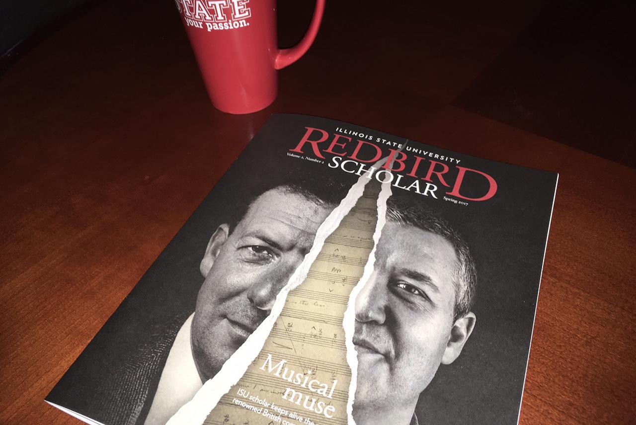 Redbird Scholar magazine on a table next to a coffee mug