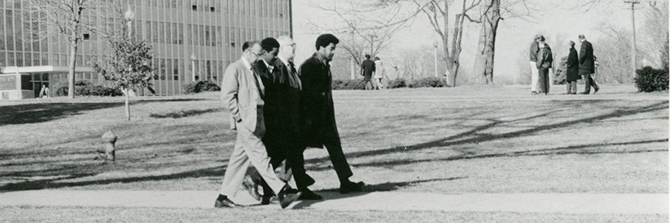 President Braden and another administrator walks with two black students on the Quad in 1969