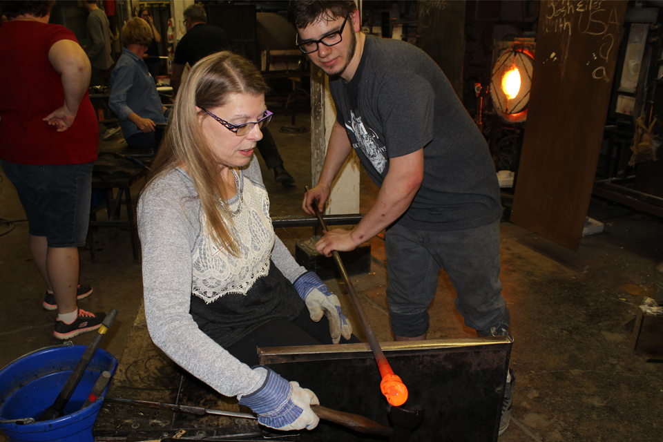 An alumna watches Tyler Wolf form a glass paperweight at an alumni event at the Glass House. Participants supported the scholarship Tyler received to travel to the Pilchuck Glass School.
