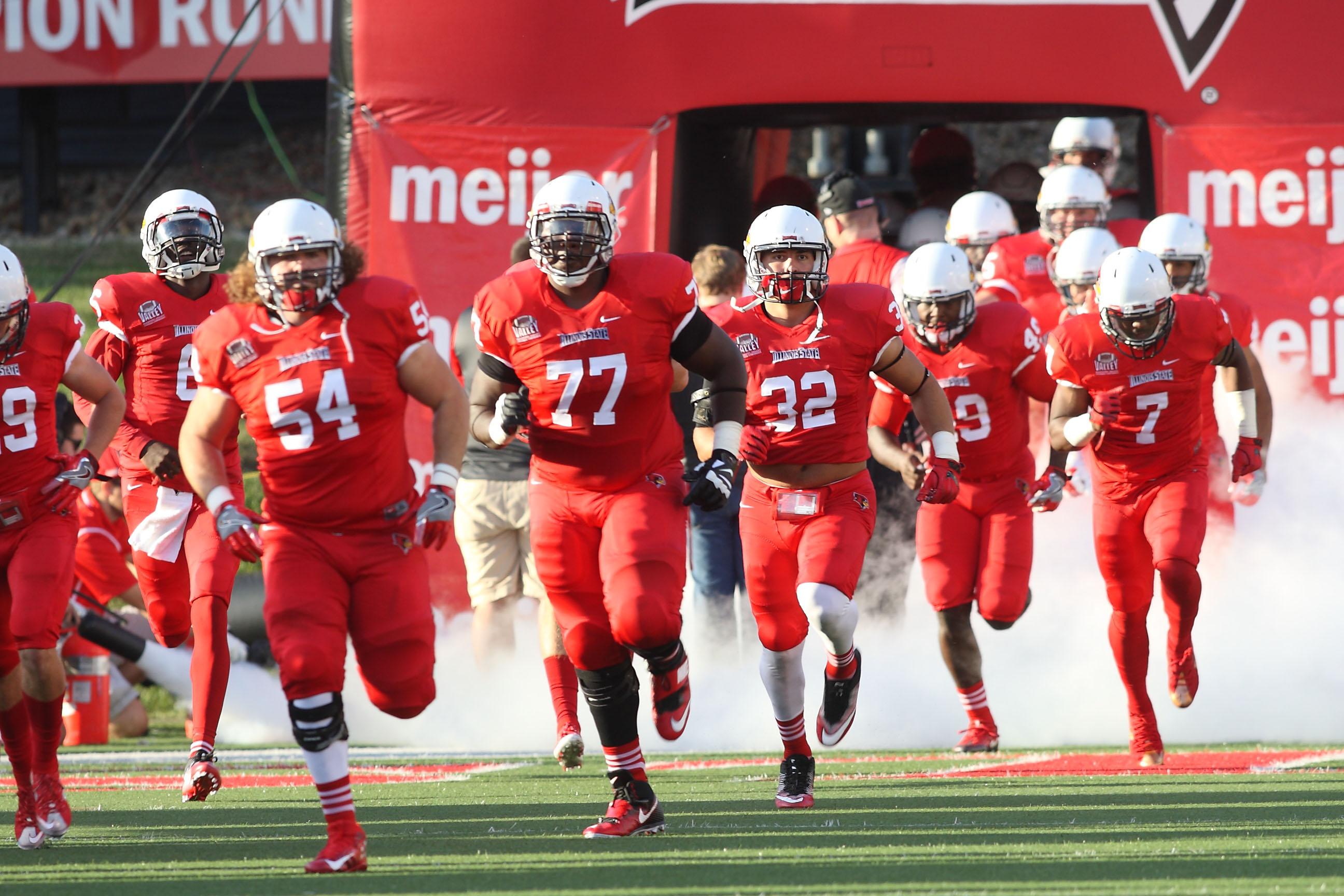 Redbird football players running onto the field