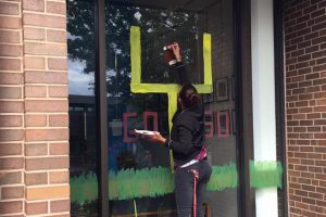 Girl painting football goal on window