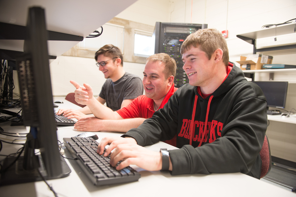 Computer Systems Technology students working with their professor.